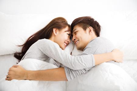 enamorados en la cama: feliz pareja encantadora joven tendido en una cama Foto de archivo
