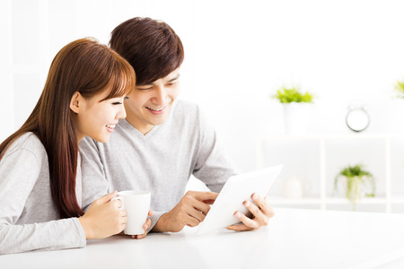 lifestyle looking lovely: happy young Couple with tablet In living room Stock Photo