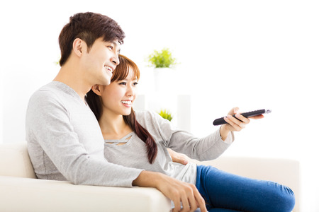 happy young couple watching tv in living room Imagens