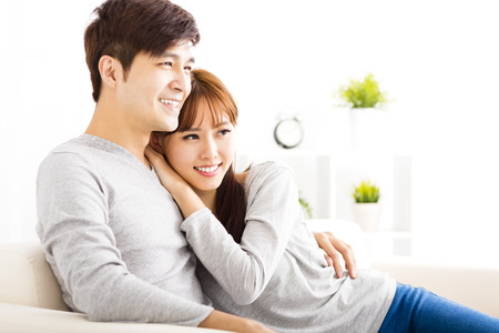 beautiful teeth: sweet young couple sitting in sofa Stock Photo