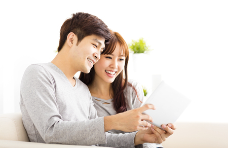 happy  Couple Looking at tablet In living room Stock Photo
