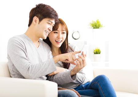 young asian couple: happy  Couple Looking at smart phone In living room Stock Photo