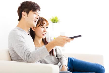 personas mirando: happy young couple watching tv in living room Foto de archivo