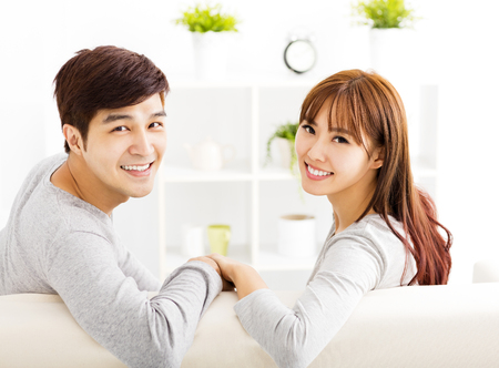 sweet young couple sitting in sofa photo