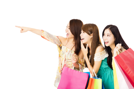 hand pointing: Group of happy young woman with shopping bags looking  something Stock Photo