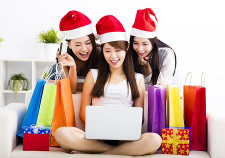 asia people: three young women watching laptop with christmas shopping concept