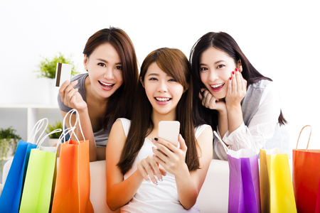 three young women with shopping bags and looking at smart phone
