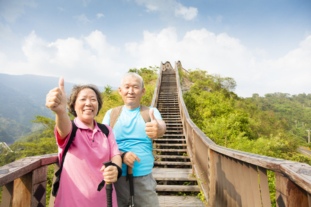 old couple walking: happy  senior couple hiking on the mountain with thumbs up