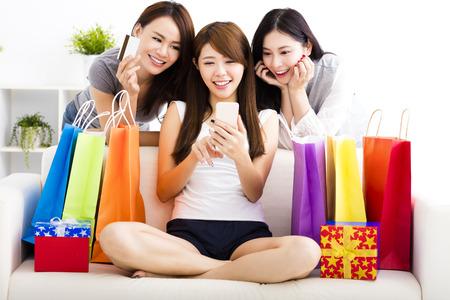 chicas compras: tres mujeres jóvenes con bolsas de compras y mirando teléfono inteligente