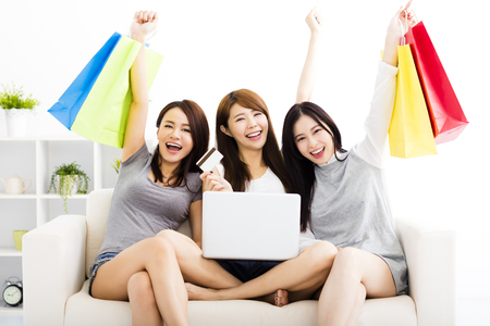 three young women watching laptop with on line shopping concept