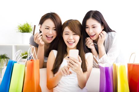 drie jonge vrouwen met boodschappentassen en kijken naar slimme telefoon