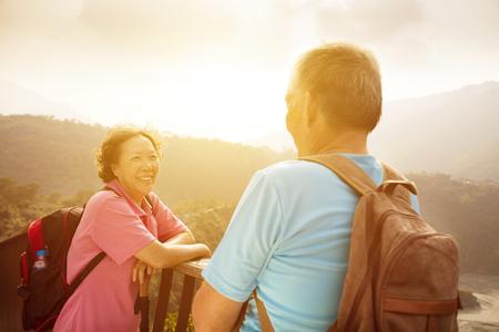 personas platicando: feliz pareja de senderismo alto en la monta�a con el fondo de la salida del sol Foto de archivo