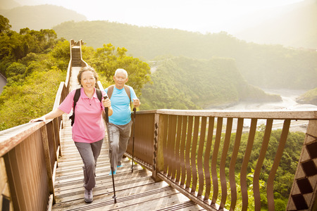 jubilados: feliz asiático pareja de ancianos senderismo en la montaña