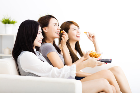 three friends: happy young woman group  eating snacks and watching the tv Stock Photo