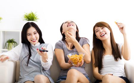 šťastná mladá žena skupina jíst lehká jídla a dívají se na televizi