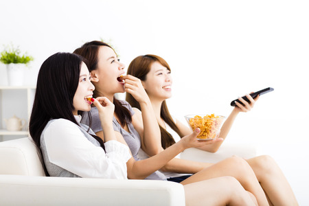 cheer: happy young woman group  eating snacks and watching the tv Stock Photo