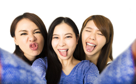 three person: young woman group having fun together and taking selfie Stock Photo