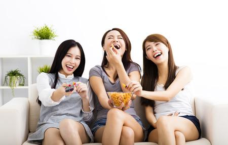 glückliche junge Frau, Gruppe essen Snacks und fernsehen Standard-Bild