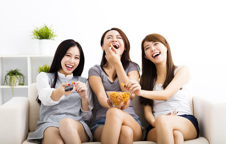 woman watching tv: happy young woman group  eating snacks and watching the tv Stock Photo