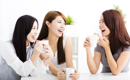 three happy young woman chatting in living room Banque d'images