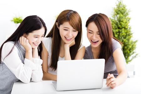 lifestyle: trois heureux jeunes femmes regardent ordinateur portable dans le salon