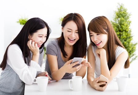 happy young women watching smart phone  in living room