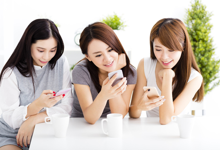 three happy young women watching smart phone  in living room