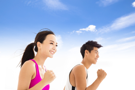 young asian couple: happy  young couple jogging against cloudy sky
