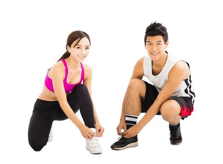 hombre deportista: Mujer y hombre atar los zapatos de los deportes antes del entrenamiento Foto de archivo