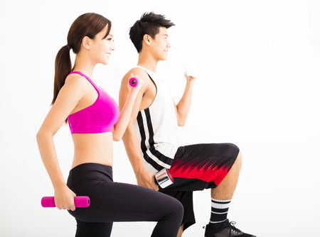 Young happy couple exercising with dumbbell Stock Photo