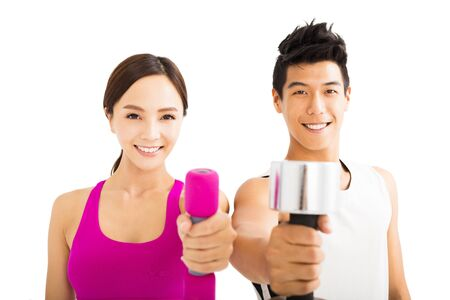 strong women: Young happy couple exercising with dumbbell Stock Photo
