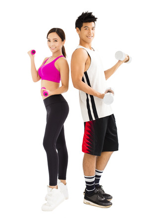 active girl: Young happy couple exercising with dumbbell Stock Photo