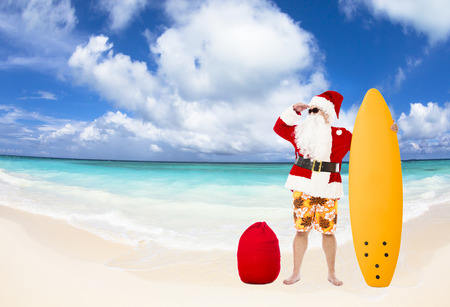 Santa Claus standing with surf board on the beach Stock Photo