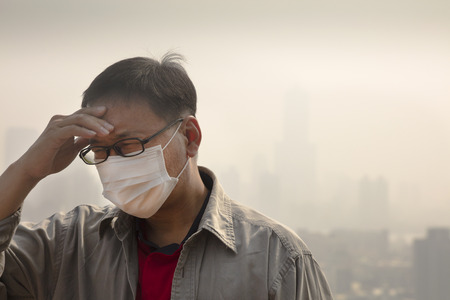 smog: Asian man wearing mouth mask against air pollution Stock Photo