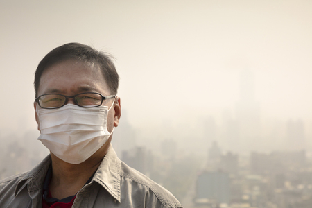 haze: Asian man wearing mouth mask against air pollution Stock Photo