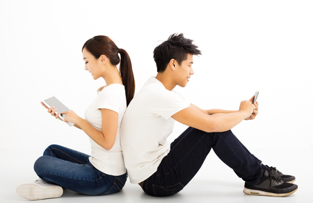 Happy young students couple with  tablet and smart phone