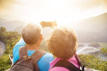 人々: 幸せな先輩カップルの山にハイキングして selfies