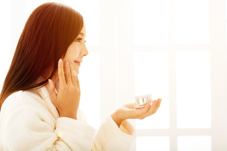 young woman face: young woman doing  makeup in front of  bathroom mirror at morning Stock Photo