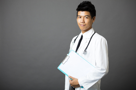 health care: Friendly young male doctor isolated on gray background