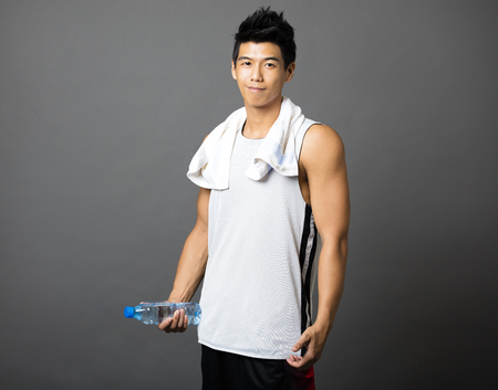 handsome young athletic: asian young man after doing exercises and holding  bottle of water