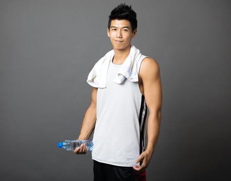 motion: asiatisk ung man efter att ha gjort övningarna och hålla flaska vatten