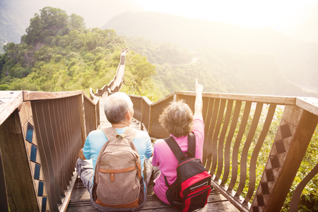 señora mayor: feliz pareja de senderismo alto en la montaña