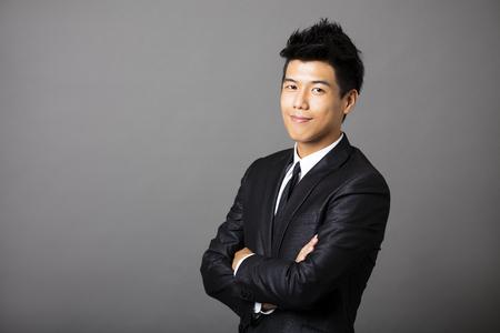 portrét: Mladý asijský podnikatel na šedém pozadí