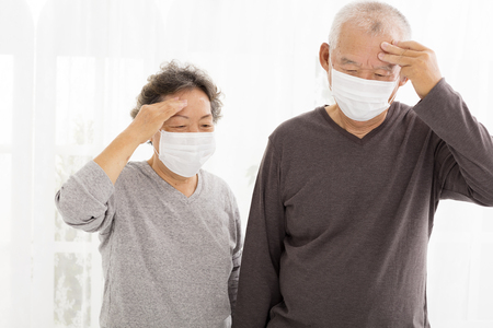 headache pain: senior couple with protective face mask