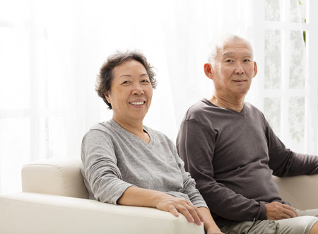 woman on couch: senior couple sitting close together on the sofa Stock Photo