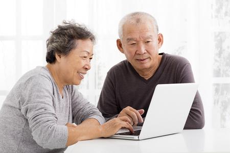 matrimonio feliz: felices Pares mayores usando la computadora portátil en la sala de estar Foto de archivo