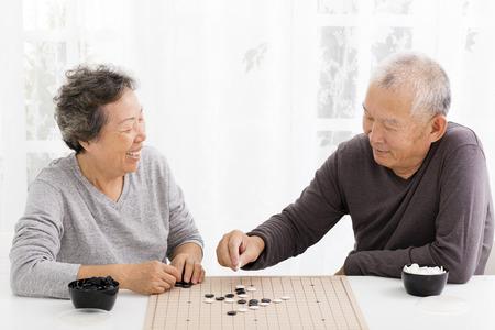 jugando ajedrez: feliz asiático mayor ajedrez pareja de juego en la sala de estar