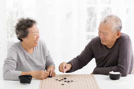 old man happy: happy asian senior couple playing chess in living room Stock Photo
