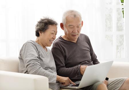 asian wife: happy Senior Couple Using Laptop on sofa