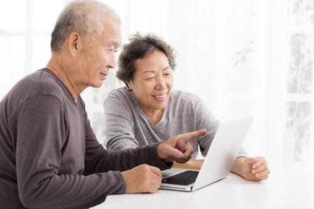 jubilados: felices Pares mayores usando la computadora portátil en la sala de estar Foto de archivo
